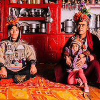 A Drokpan couple sitting in their kitchen-cum-drawing-room. Most of the ladakhi houses have a large kitchen where there is ample room for guests to sit, relax and have their meals and Drokpan kitchens are no different as they follow Buddhist religion.