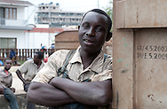 "MWANZA, TANZANIA.  A railway worker who gave his name as ""Matthew"" pauses for a portrait in a train yard in Mwanza, Tanzania on Friday, September 5, 2014. The workers are part of a crew of laborers who load creosote poles onto railroad cars by hand.  © Chet Gordon/THE IMAGE WORKS"