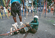 "Trinidad and Tobago ""MOKO JUMBIES: The Dancing Spirits of Trinidad"".(A Moko Jumbie sits on the pavement on Henry Street during a parade. The cut off car seat belt, which is tied around the lower leg, sometimes loosen and has to be tightened. A handler stands by to guard her , and he will lift her up again when ready. His main tool, a hammer, is used to nail the belt onto the wooden stilt.).A photo essay about a stilt walking school in Cocorite, Trinidad..Dragon Glen de Souza founded the Keylemanjahro School of Art & Culture in 1986. The main purpose of the school is to keep children off the streets and away from drugs..He first taught dances like the Calypso, African dance and the jig with his former partner Cathy Ann Samuel.  Searching for other activities to engage the children in, he rediscovered the art of stilt-walking, a tradition known in West Africa as the Moko Jumbies , protectors of the villages and participants in religious ceremonies. The art was brought to Trinidad by the slave trade and soon forgotten..Today Dragon's school has over 100 members from age 4 and up..His 2 year old son Mutawakkil is probably the youngest Moko Jumbie ever. The stilts are made by Dragon and his students and can be as high as 12-15 feet. The children show their artistic talents mostly at the annual Carnival, which today is unthinkable without the presence of the Moko Jumbies. A band can have up to 80 children on stilts and they have won many of the prestigious prizes and trophies that are awarded by the National Carnival Commission. Designers like  Peter Minshall , Brian Mac Farlane and Laura Anderson Barbata create dazzling costumes for the school which are admired by thousands of  spectators. Besides stilt-walking the children learn the limbo dance, drumming, fire blowing and how to ride  unicycles..The school is situated in Cocorite, a suburb of Port of Spain, the capital of Trinidad and Tobago..all images © Stefan Falke"