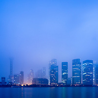 China, Shanghai, Skyscrapers in skyline of Pudong District lost in low clouds along Huangpu River on winter morning