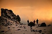 Mountaineers watch an approaching evening storm, from camp at 4850m (15,915ft) below Arrow Glacier and Western Breach, Kilimanjaro, Tanzania. 0-deg 10-min South of Equator. Nikon F4, 35-135/3.5-4.5. Kodak E100SW. January 1997.