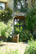 A Gothic Cotswold stone seat and tiers of Gothic tracery windows in a courtyard in the abbey ruins at Sudeley Castle, Gloucestershire. <br />