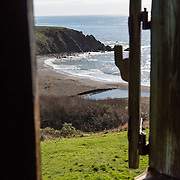 """In Sandy Cove, pictured through a blockhouse window of Fort Ross, the Russian-American Company made the first four ships built in (Alta) California. Fort Ross State Historic Park preserves a former Russian colony (1812-1842) on the west coast of North America, in what is now Sonoma County, California, USA. Visit Fort Ross and dramatic coastal scenery 11 miles north of Jenner on California Highway One.  Initially, sea otter pelts funded Russian expansion, but by 1820, overhunting motivated the Russian-American Company to introduce moratoriums on hunting seals and otters, the first marine-mammal conservation laws in the Pacific. Russian voyages greatly expanded California's scientific knowledge. For centuries before Europeans arrived, this site was called Metini and had been occupied by the Kashaya band of Pomo people who wove intricate baskets and harvested sea life, plants, acorns, deer, and small mammals. Sponsored by the Russian Empire, """"Settlement Ross"""" was multicultural, built mostly by Alaskan Alutiiq natives and occupied mostly by native Siberians, Alaskans, Hawaiians, Californians, and mixed Europeans. Renamed """"Ross"""" in 1812 in honor of Imperial Russian (Rossiia), Fortress Ross was intended to grow wheat and other crops to feed Russians living in Alaska, but after 30 years was found to be unsustainable. Fort Ross was sold to John Sutter in 1841, and his trusted assistant John Bidwell transported its hardware and animals to Sutter's Fort in the Sacramento Valley. Fort Ross is a landmark in European imperialism, which brought Spanish expanding west across the Atlantic Ocean and Russians spreading east across Siberia and the Pacific Ocean. In the early 1800s, Russians coming from the north met Spanish coming from the south along the Pacific Coast of California, followed by the USA arriving from the east in 1846 for the Mexican-American War. Today, Fort Ross is a California Historical Landmark and a National Historic Landmark."""