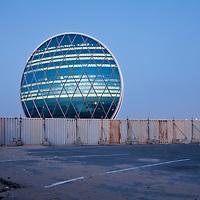 United Arab Emirates, Abu Dhabi, Construction fence surrounds The Disc building in Khalifa City at dusk
