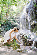 In praise of water by Nano Calvo<br /> A beautiful young woman touches the fresh waters that come down from a waterfall