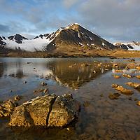 Norway, Svalbard, Spitsbergen, Rising midnight sun lights glacier-covered mountains along Krossfjorden at Signehamna Harbor