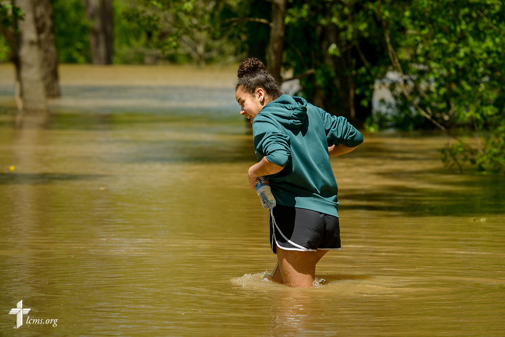 Volunteer Abbey Gierer wades through flood waters during a short break in sandbagging for church member Ruth Houser at her home on Tuesday, May 2, 2017, in Arnold, Mo. Fellow volunteers from nearby St. John's Lutheran Church, Arnold, filled sandbags as rising waters advanced toward's Houser's home. LCMS Communications/Erik M. Lunsford