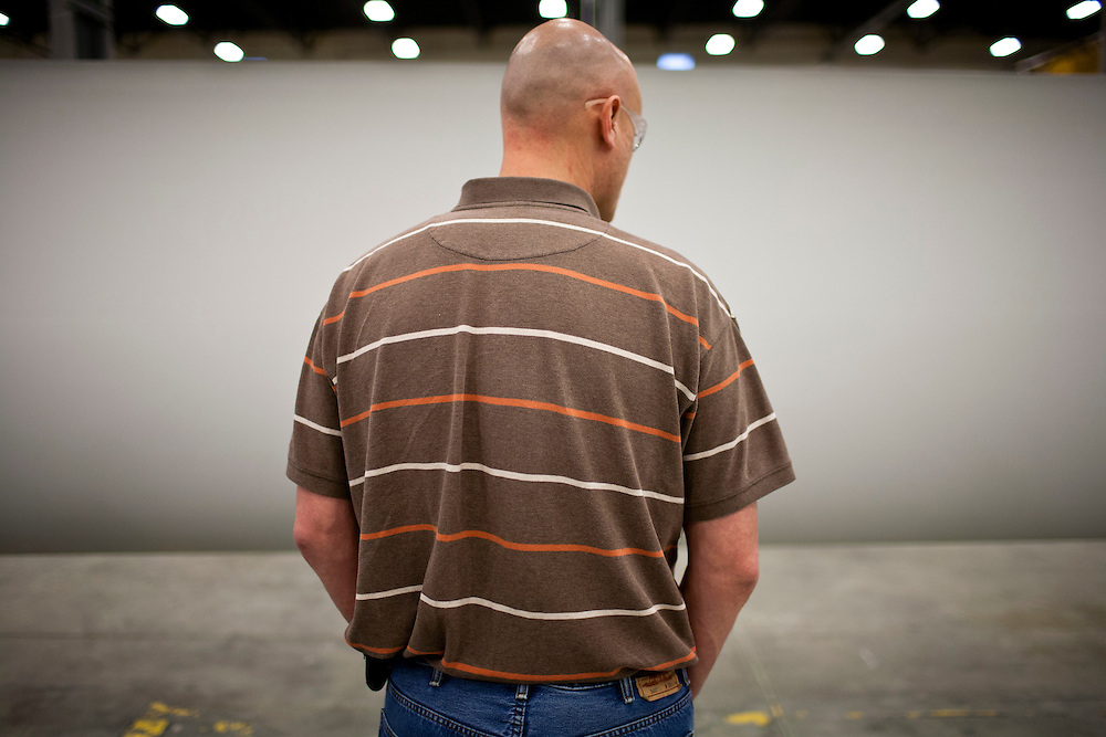 A worker looks at a wind turbine blade as Republican presidential candidate Rick Perry speaks at an employee town hall at TPI Composites on Thursday, December 22, 2011 in Newton, IA.