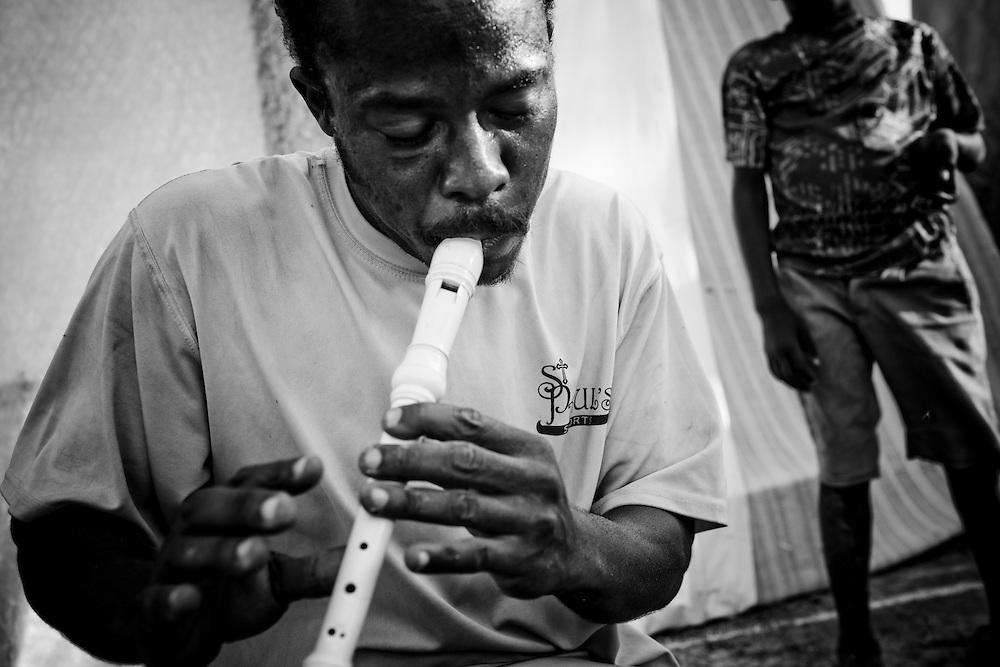 A man plays a recorder in a camp for those displaced by the recent earthquake in Petionville, outside Port-au-Prince, Haiti.