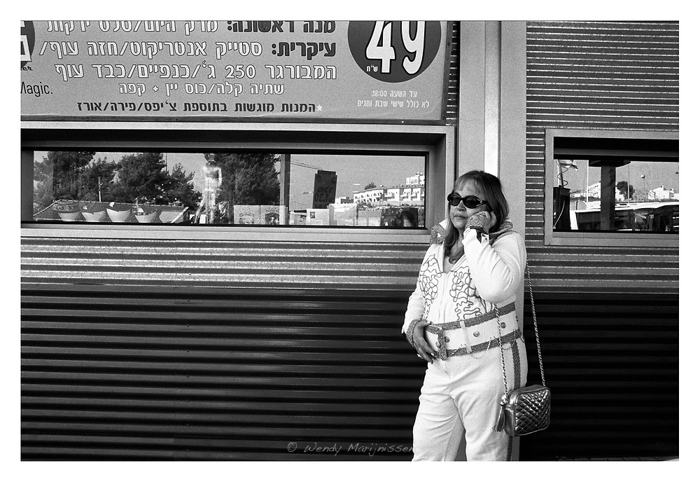 A female Elvis impersonator making a call outside the roadside restaurant Elvis Inn, on the day Elvis Presley died and which is celebrated yearly all over the world. Jerusalem, Israel, 2007