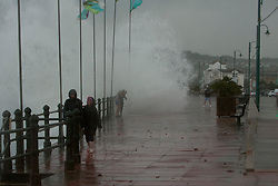 © Licensed to London News Pictures. 15/08/2012. Penzance, UK. Members of the public are caught in a wave crashing over Penzance Promenade. The Police closed the road due to the waves crashing over the road due to high winds but many motorist ignored the warnings. Photo credit : Ashley Hugo/LNP
