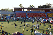 Teens play soccer on the fake turf at Port-au-Prince's soccer stadium -- the rest of the field has been converted into a tent city.