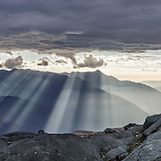 Spectacular rays of afternoon light pierce clouds over the Cordillera Negra and spotlight the Santa Valley (historically known as Callejon de Huaylas/Alley of Huaylas) in the Ancash Region in the north-central highlands of Peru. The viewpoint is from Lake Cullicocha, high above Hualcayan village. This was day 8 of 10 days trekking around Alpamayo in Huascaran National Park (UNESCO World Heritage Site), Cordillera Blanca, Andes Mountains, Peru, South America. This panorama was stitched from 4 overlapping photos.