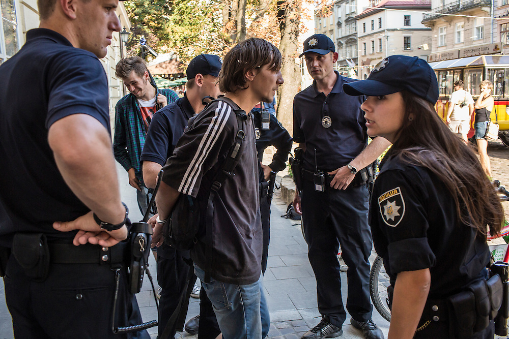 LVIV, UKRAINE - SEPTEMBER 16, 2015: Members of the new Lviv police, including Tetiana Soroka, 25, right, arrest Vladimir, 26, after he was found intoxicated and sleeping in the city's central square and then swore at police officers in Lviv, Ukraine. In an effort to reform the notoriously corrupt Ukrainian police force, an entirely new force has been established in several cities, including Kiev and Lviv, with a primary focus on patrolling the streets. CREDIT: Brendan Hoffman for The New York Times