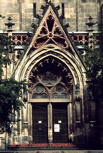West Door of Thomaskirche in Leipzig, Germany where Johann Sebastian Bach worked between 1723 and 1750.  Undernaeth the pointed gable, an elaborate structural detail including an arched doorway, three windows including a circular one and two gothic doors.