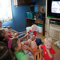 """Jeub family members watch the Steve Martin movie """"Cheaper By The Dozen"""" (2003) about a man with 12 children at the family home in Monument, Colorado July 17, 2009. (L-R) Tabitha, 9; Havilah, 3; Hannah, 6; Keilah, 8; Cynthia; Josiah, 5; Noah, 10. Quiverfull believers Wendy and Chris Jeub have 15 children and would be happy to have more if God wills it they say. Two of the 15 children have moved out. Picture taken July 17, 2009.  REUTERS/Rick Wilking (UNITED STATES SOCIETY RELIGION)"""