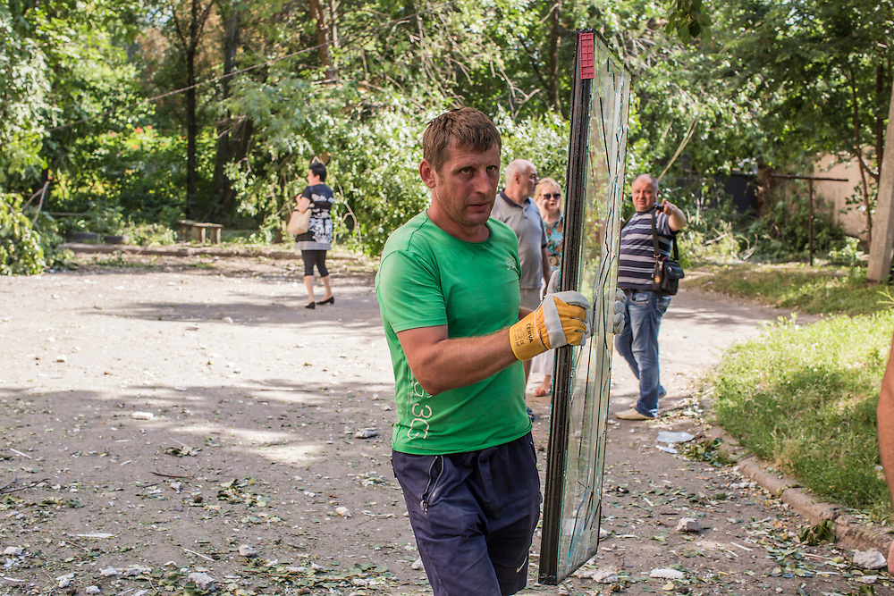 A man carries a broken window from an apartment building that was hit by a suspected grad rocket strike on Tuesday, July 29, 2014 in Donetsk, Ukraine.
