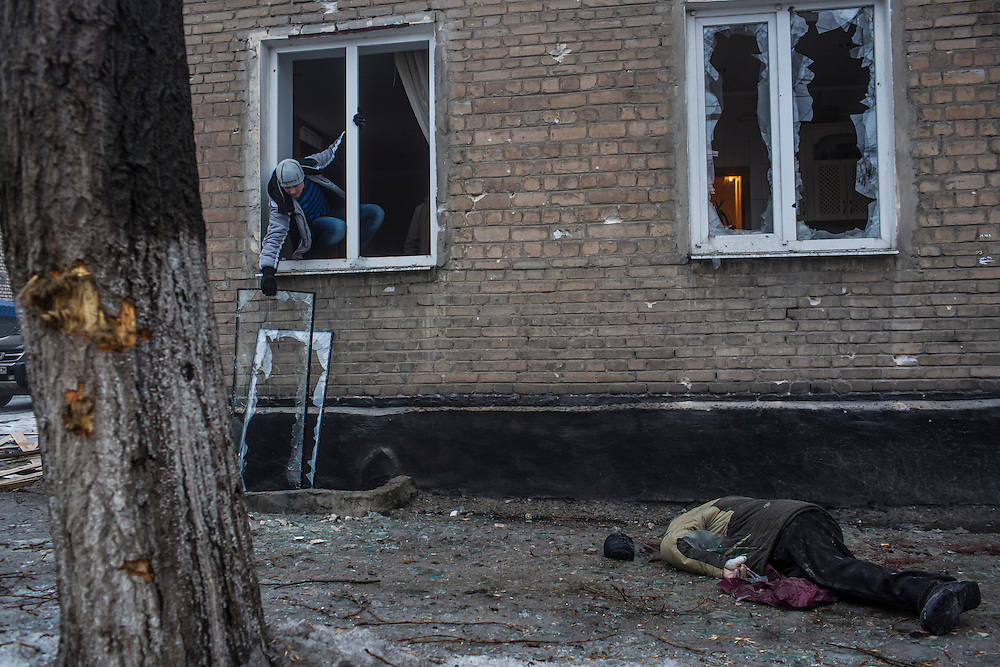DONETSK, UKRAINE - JANUARY 30, 2015: The body of a man lies on the sidewalk as another man removes a broken window pane from its frame in Donetsk, Ukraine. A rocket or mortar struck the road, breaking the windows and killing at least two men on the sidewalk. At least five people were killed in a separate attack nearby when a rocket struck the parking lot outside a center for the distribution of humanitarian aid. CREDIT: Brendan Hoffman for The New York Times