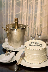 """Cake decorated with """"Happy Anniversary"""" on a table with Champagne bucket, two champagne flutes, Champagne bottle and silverware"""