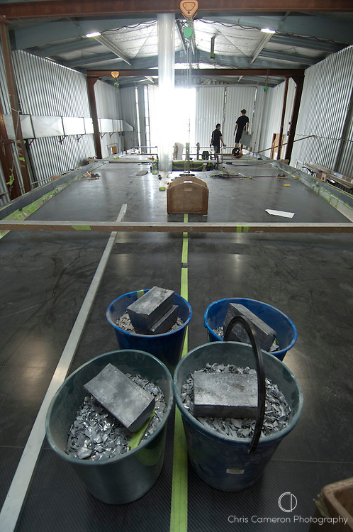 Buckets of Lead hold the deck down as the resin dries. The Camper Emirates Team New Zealand VO70 under construction at Cookson boats in Auckland. 15/12/2010