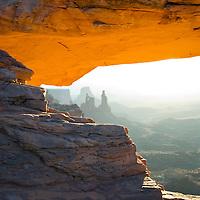 An orange glow illuminates Mesa Arch at sunrise, Canyonlands National Park, Utah