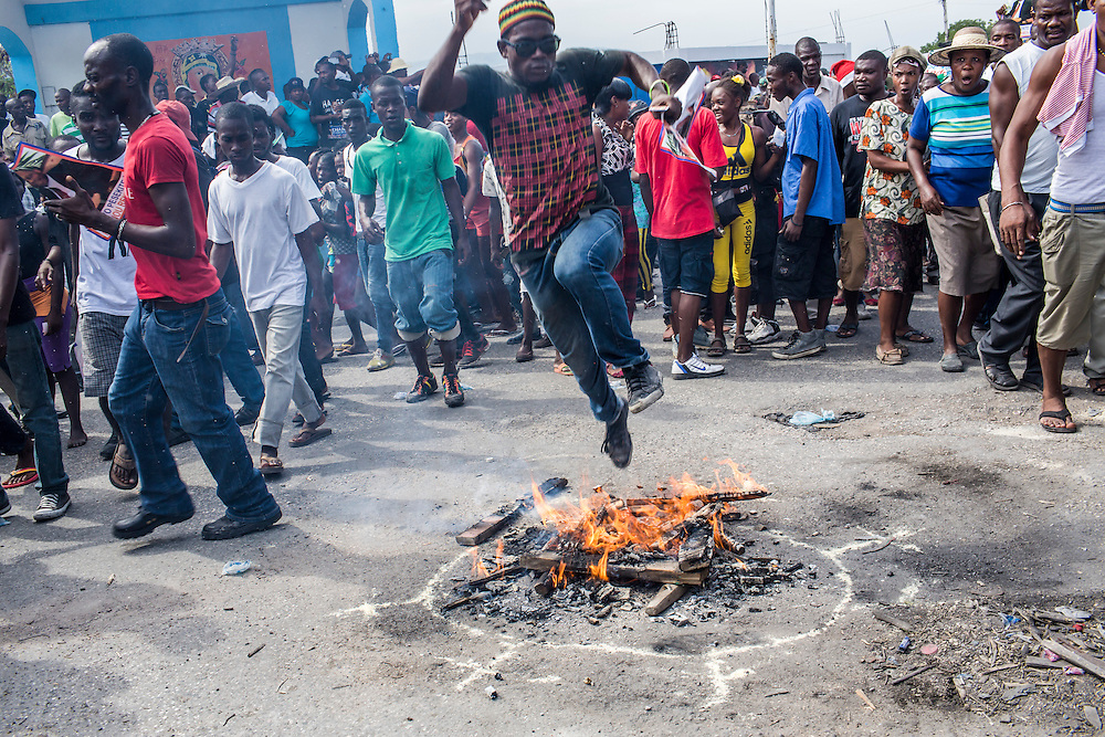 A man leaps over a fire, part of a Haitian vodou cultural ritual, at the start of an anti-government protest on Tuesday, December 16, 2014 in Port-au-Prince, Haiti. President Michel Martelly was elected in 2010 with great hope for reforms, but in the wake of slow recovery and parliamentary elections that are three years overdue, his popularity has suffered tremendously, forcing Prime Minister Laurent Lamothe to resign.