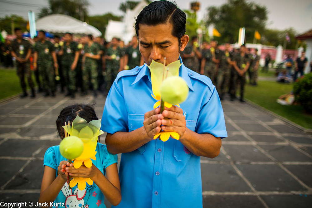 """25 FEBRUARY 2013 - BANGKOK, THAILAND:   A man and his daughter pray in front of a group of Thai soldiers at Wat Benchamabophit Dusitvanaram (popularly known as either Wat Bencha or the Marble Temple) on Makha Bucha Day. Makha Bucha is a Buddhist holiday celebrated in Myanmar (Burma), Thailand, Cambodia and Laos on the full moon day of the third lunar month (February 25 in 2013). The third lunar month is known in Thai is Makha. Bucha is a Thai word meaning """"to venerate"""" or """"to honor"""". Makha Bucha Day is for the veneration of Buddha and his teachings on the full moon day of the third lunar month. Makha Bucha Day marks the day that 1,250 Arahata spontaneously came to see the Buddha. The Buddha in turn laid down the principles his teachings. In Thailand, this teaching has been dubbed the 'Heart of Buddhism'.    PHOTO BY JACK KURTZ"""