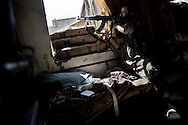 SYRIA, ALEPPO, A Free Syrian Army (FSA) sniper takes aim at an army position in Aleppo's old city on September 24, 2012. FSA snipers take position on abandoned apartment of Aleppo's old city over-looking regime checkpoints, preventing soldiers to move toward rebel-controlled areas.. ALESSIO ROMENZI