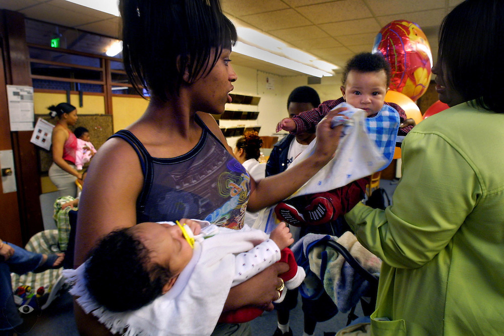 LaTasha Taylor gets a little baby help from Tonya Dickens during a meeting of the Youth Gangs Program out of King School, Sister's Keepers.