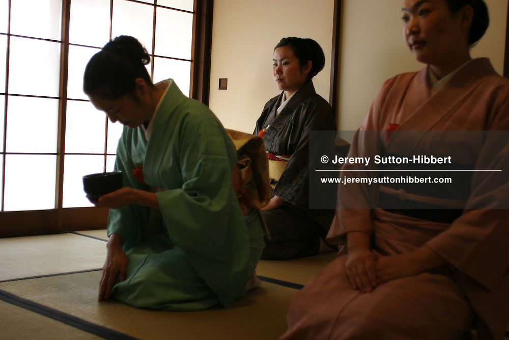 "A student holds a cup, whilst practicing her 'tea ceremony' skills. The art of the ""tea ceremony', as practiced at the Chadou-Kaikan, a school to teach the traditional tea ceremony skills. Pupils attend to learn the tea making skills, and also about Japanese history, tradition and manners. Takadanobaba, Tokyo, Japan"