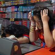Krystal Leon, 17,  looks at her reflection in the mirror inside the grocery scanner in between customers while bagging groceries during her cashier shift at Steve's C-Town, a grocery store on 9th Street between 5th and 6th Avenues in Park Slope, Brooklyn on June 8, 2007. <br /> <br /> photo by Angela Jimenez for The New York Times<br /> photographer contact 917-586-0916