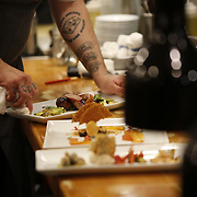 SHOT 8/14/13 7:01:17 PM - Justin Brunson, Owner and Executive Chef at Old Major restaurant in Denver, Co. Includes images of menu items : The Nose to Tail Plate : confit rib, pork chop, crispy belly, city ham, crispy ear, Denver Bacon Co. barbecue beans, cole slaw and corn bread $29 and Pan Seared Scallops : baby vegetables, fregola, spinach purée, toasted pine nuts, roasted garlic vinaigrette $27. The restaurant focuses on heritage-raised meats from Colorado farms, features an in-house butchery program and bills itself as contemporary farmhouse cuisine. (Photo by Marc Piscotty / © 2013)