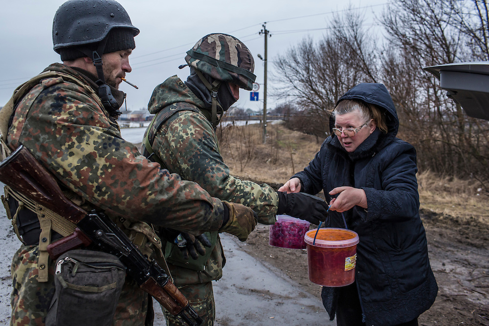SARTANA, UKRAINE - FEBRUARY 5, 2015: A woman delivers food to members of the St. Mary's Battalion, a pro-Ukraine militia, at a checkpoint in Sartana, Ukraine. With more than 220 people having died in the past several weeks, a new diplomatic push is underway to bring an end to fighting between pro-Russia rebels and Ukrainian forces. CREDIT: Brendan Hoffman for The New York Times