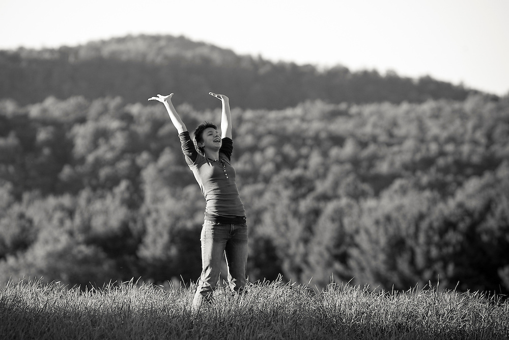 A young woman stands in a field with her arms extended to the sky, Vermont