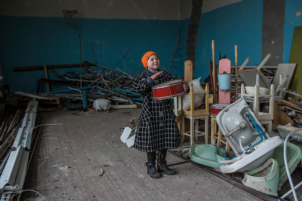 A student plays with a drum found amid items stored in the gymnasium of a school, which was hit by a shell earlier in the year and heavily damaged, on Friday, December 11, 2015 in Troitske, Ukraine.