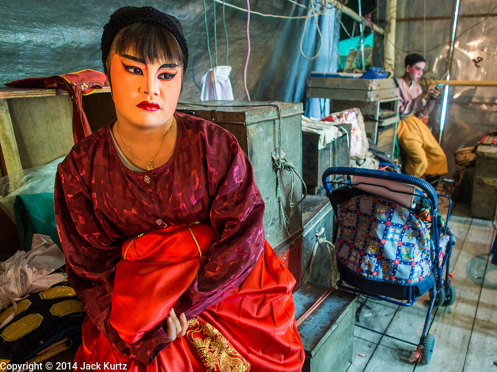 """25 JANUARY 2014 - BANG LUANG, NAKHON PATHOM, THAILAND: Performers with the Sing Tong Teochew opera troupe relax backstage during a show in a Chinese shrine in the town of Bang Luang, Nakhon Pathom, Thailand. The Sing Tong Teochew opera troupe has been together for 60 years and travels through central Thailand and Bangkok performing for mostly ethnic Chinese audiences. Chinese opera was once very popular in Thailand, where it is called """"Ngiew."""" It is usually performed in the Teochew language. Millions of Chinese emigrated to Thailand (then Siam) in the 18th and 19th centuries and brought their cultural practices with them. Recently the popularity of ngiew has faded as people turn to performances of opera on DVD or movies. There are still as many 30 Chinese opera troupes left in Bangkok and its environs. They are especially busy during Chinese New Year when travel from Chinese temple to Chinese temple performing on stages they put up in streets near the temple, sometimes sleeping on hammocks they sling under their stage.     PHOTO BY JACK KURTZ"""