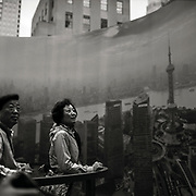 Woman stands in center of 'Amazing Shanghai'exhibit in Rockefeller Center in front of German photographer HG Esch's 360-degree panorama view of the city of Shanghai, consisting of 60 images taken this year from Shanghai's Jin Mao Tower in the new district of Pudong on the bank of the Huangpu River.
