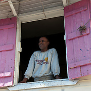 Mauritius. Man in window of old creole house. Port Louis..