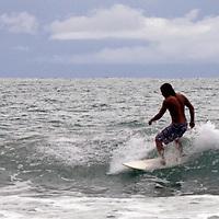 Central America, Costa Rica, Manuel Antonio.  Surfer at Manuel Antonio.
