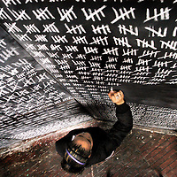 Iris Encarnacion, 17, a student from the Boston Day Evening Academy, makes chalk marks  to symbolize the number of AIDS and HIV infections in the world as part of Medicine Wheel's sculptural installation at the Boston Center for the Arts on World AIDS Day, Wednesday.