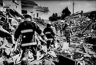 Rescue workers move slowly through houses that were ripped from their foundations by the great tsunami to painstakingly search uprooted, empty houses for victims.  Ofunato, Iwate Prefecture, Japan.