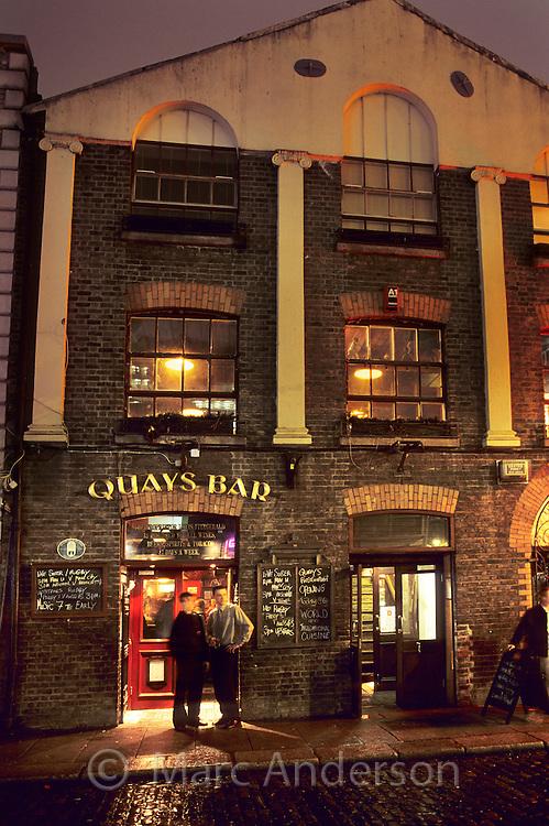 Men standing outside Quays Bar at night, Dublin, Ireland.