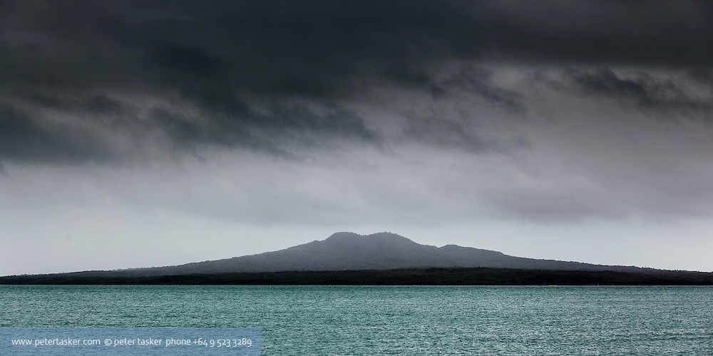 Rangitoto Island, partially covered in rain, with cloud hanging above and aqua blue seas below.