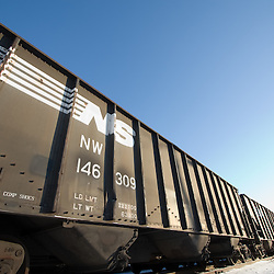 A wide angle view of a train of coal hoppers with copy space above.