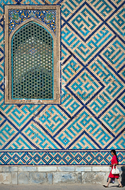 Samarkand. Woman walking beside the Registan walls