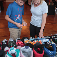 Xavier Smith, 11, and his mother Amber Sheets look at a display of shoes during Sneaker Jam Sunday July 20, 2014 at Carolina Club 1880 in Wilmington, N.C. The event offered sneaker collectors the opportunity to purchase and trade new and rare shoes. (Jason A. Frizzelle)