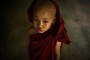 A very young monk passes through the halls of the monastery as most others are in classes.
