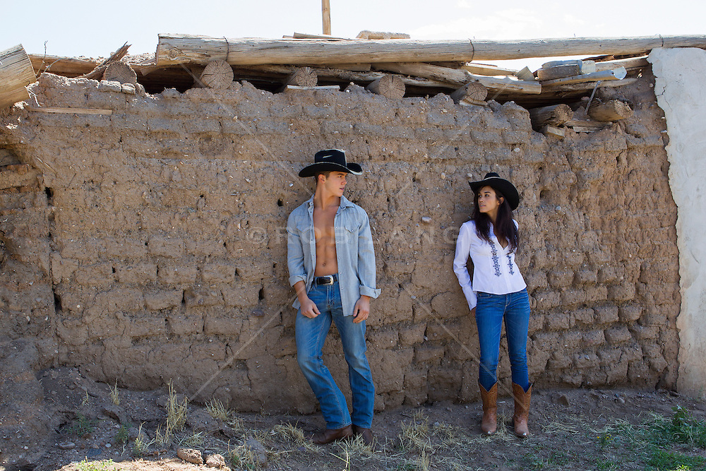 cowboy and a girl together on a ranch in New Mexico leaning against an adobe building