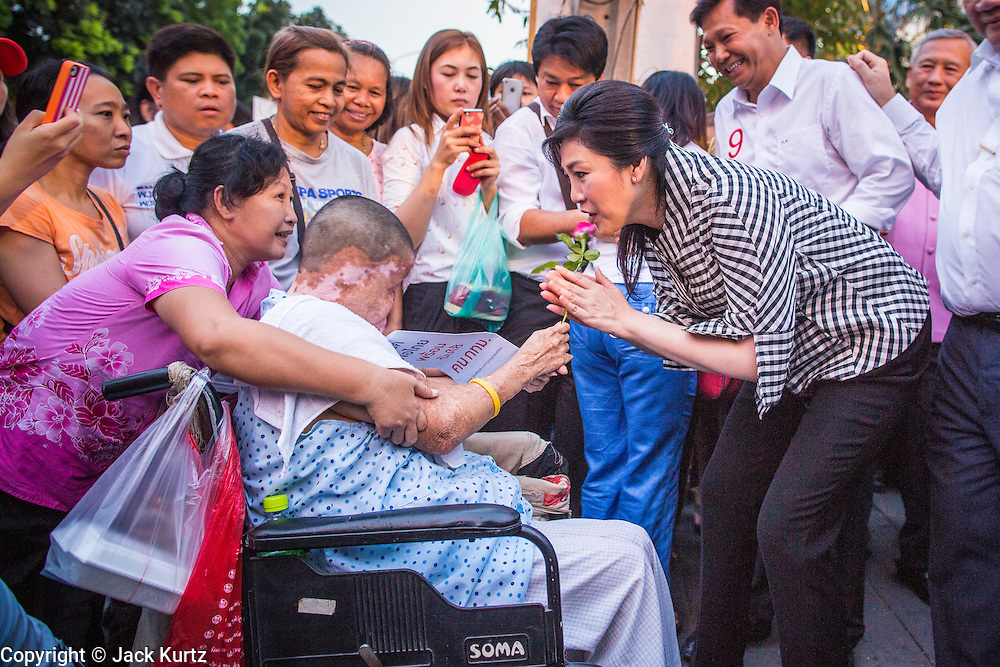 27 FEBRUARY 2013 - BANGKOK, THAILAND:  YINGLUCK SHINAWATRA, Prime Minister of Thailand, (right) talks to a severely burned woman while she campaigns for Pongsapat Pongchareon's election to Governor of Bangkok. Police General Pongsapat Pongcharoen (retired), a former deputy national police chief who also served as secretary-general of the Narcotics Control Board is the Pheu Thai Party candidate in the upcoming Bangkok governor's election. (He resigned from the police force to run for Governor.) Former Prime Minister Thaksin Shinawatra reportedly personally recruited Pongsapat. Most of Thailand's reputable polls have reported that Pongsapat is leading in the race and likely to defeat Sukhumbhand Paribatra, the Thai Democrats' candidate and incumbent. The loss of Bangkok would be a serious blow to the Democrats, whose base is the Bangkok area.    PHOTO BY JACK KURTZ