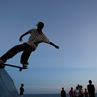 Africa, Mozambique, Maputo, Silhouette of skateboarder riding along crowded beach at dusk